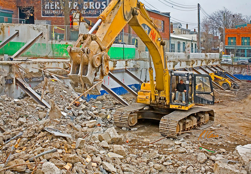 Demolition/concrete construction: Caterpillar 345BL track mounted hydraulic backhoe excavator fitted with pulverizer attachment picks reinforcing bars out of debris pile and transports bars to the bar shear/lopper to be cut into smaller pieces. This muncher is responsible for munching the old concrete off the reinforcing bars so the resteel can be sheared and recycled. Old City parking garage, Washington and First, Ann Arbor, Michigan, February 2006.