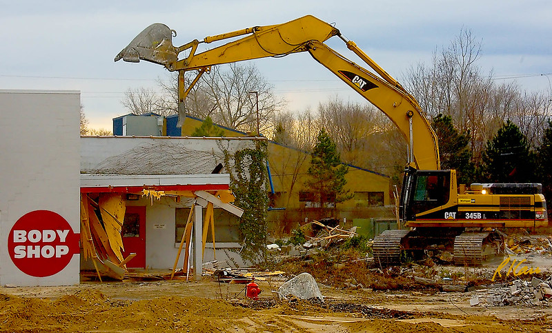 Caterpillar 345B backhoe with grappler bucket descending with thumb extended to pierce and cave in top of porch overhang of car dealer body shop early in building demolition. Washtenaw near Huron Parkway, Ann Arbor, Michigan. January, 2007.