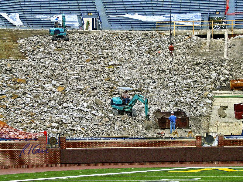 Stadium construction: Reconstruction of spectator seating. Upper portion is new seating. Left mid-upper is old concrete with seats removed, and backhoe with pavement breaker attachment, demolishing old concrete. Main area is demolished seating base concrete. Right mid-upper is concrete stair stringers, not yet demolished. Backhoe in foreground loads rectangular debris bucket that crane will then raise and dump outside stadium. The Big House, Michigan Stadium, University of Michigan, Ann Arbor, 2004.