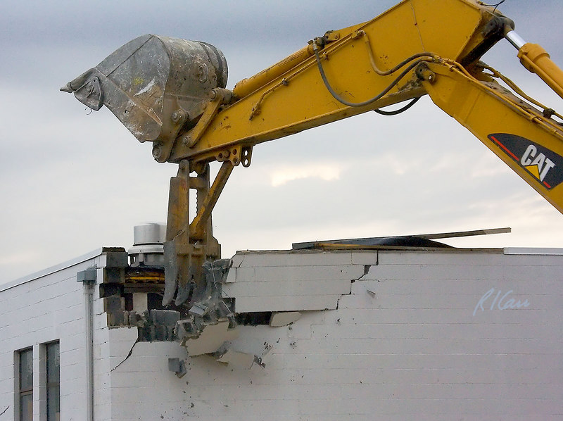 Caterpillar 345B backhoe uses thumb of grappler bucket to pull down top of load bearing concrete block masonry wall. Concrete block structure supports bar joist roof structure.  Washtenaw near Huron Parkway, Ann Arbor, Michigan. January, 2007.