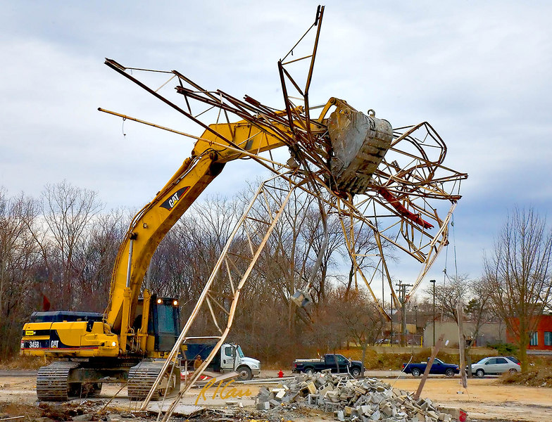 """Caterpillar 345B backhoe lifts a giant """"hand full"""" of roof open steel web joists with its grappler bucket and is turning and traveling to the debris dumpster into whiich it will cram the joists along with other steel demolition debris. Below the bucket is a pile of concrete block masonry debris. Washtenaw near Huron Parkway, Ann Arbor, Michigan. January, 2007."""