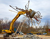 "Caterpillar 345B backhoe lifts a giant ""hand full"" of roof open steel web joists with its grappler bucket and is turning and traveling to the debris dumpster into whiich it will cram the joists along with other steel demolition debris. Below the bucket is a pile of concrete block masonry debris. Washtenaw near Huron Parkway, Ann Arbor, Michigan. January, 2007."