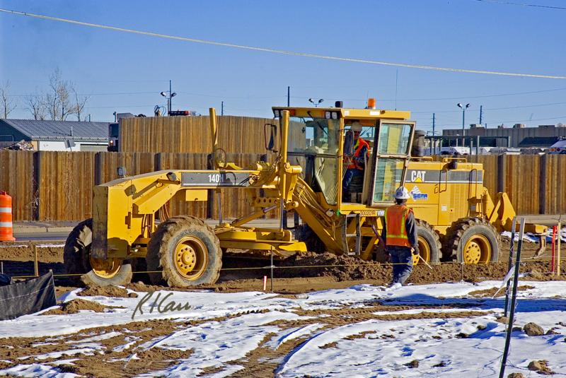 Caterpillar 140H motor grader does fine grading of soil for city street with its blade, Denver, Colorado, 2006
