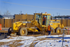 Caterpillar 140H motor grader does fine grading of soil for city street with its blade, Denver, Colorado, 2006