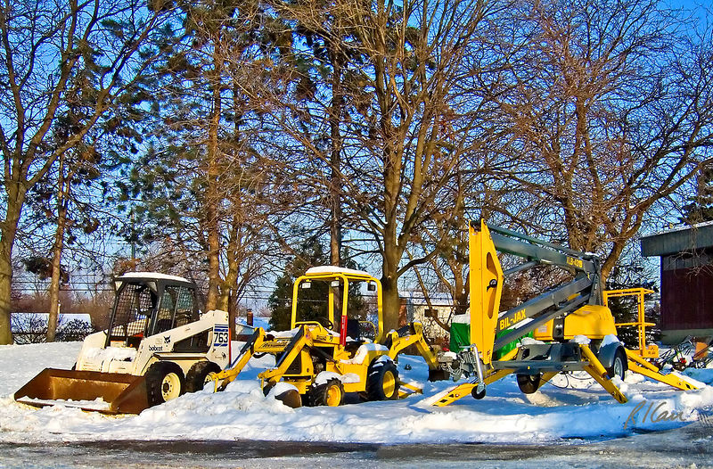 Earth moving construction, personnel lift: Construction equipment for rent at hardware store. Bobcat 763 loader with 1,500 lb/ 680 kg capacity, 46 hp/ 34 kw liquid-cooled diesel engine on left. Terramite T7 backhoe/loader excavator with with 26 hp diesel engine in center. Bil-Jax XLB-4319 articulating boom lift at right has 43 ft working height, 19 ft side outreach, 700 degree rotation, outriggers, and 450 lb capacity. Ann Arbor, Michigan December 2005