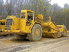 Earthmoving construction: Caterpillar 613D motor scraper, 75,000 pound payload, 31 CY heaped. Note that this is not self-loading. Machine depends on its own power plus push from a bull dozer, typically, to scrape earth into its pan. New Ann Arbor High School, Michigan 2006