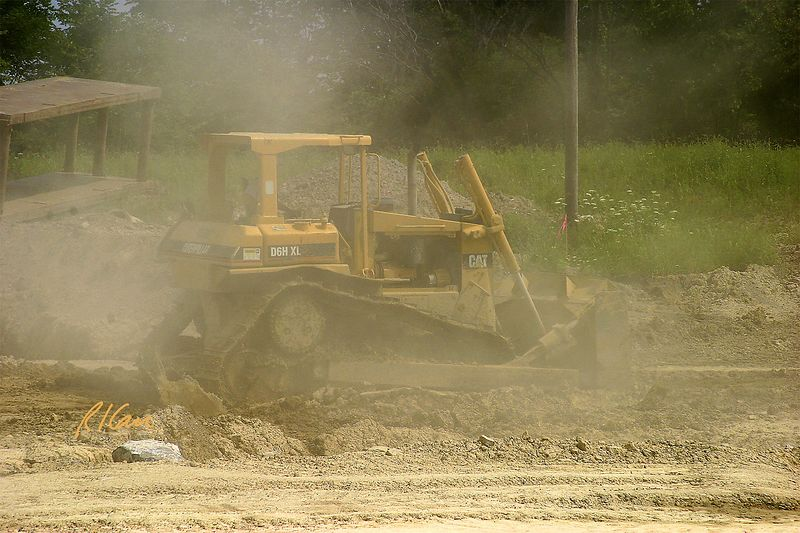 Caterpillar D6H XL crawler tractor bulldozer traveling in its own dust, compacting top of soil for better runoff of predicted rain. Hyndai Automotive Tech Center, east of Ann Arbor, 2004.
