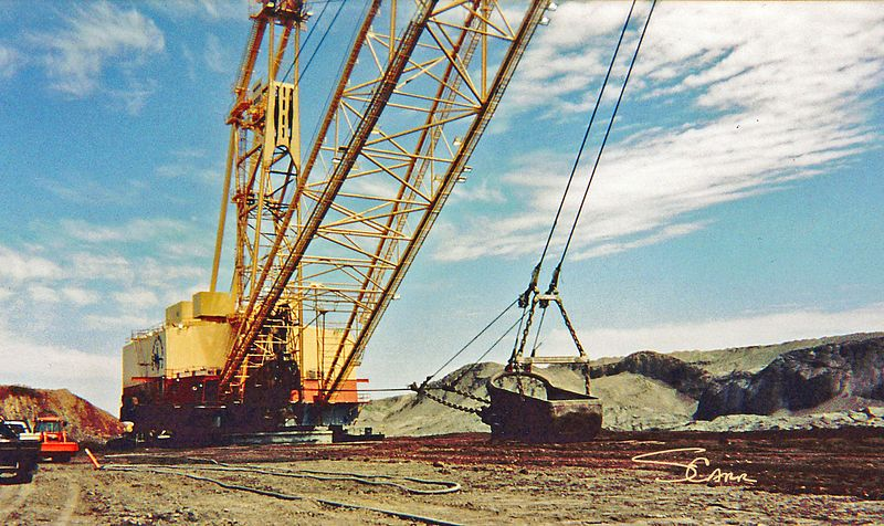 Earthmoving construction: Large drag line removes overburden of earth on top of coal beds to expose the coal so it can be strip mined. Note size of bucket relative to equipment on left. Wyoming mine operated by Kennecott Energy, 2002. Photo by Scott M. Carr