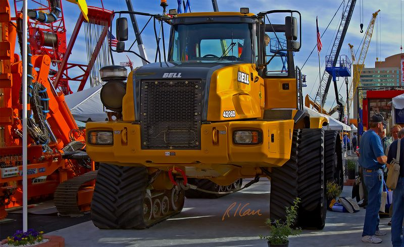 """Earthmoving construction: Bell 4206D/T rubber track scraper towing tractor develops 65,000 lb of drawbar pull, will tow 3 fully loaded 18 CY scrapers in rough terrain. The 4206D/T replaces the 4 wheels of the 4206D tractor with 4 ATI 6,000 lb individual track assemblies having 36"""" wide continuous tracks (note in photo). CONEXPO, Las Vegas, Nevada, March 15-19, 2005."""