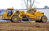 Soil, earth construction: Caterpillar 613C elevating/self-loading scraper, 11 CY capacity, 175 hp, is moving earth to level land to a more even grade for construction of condominiums. Soil, earth construction: Caterpillar 613C elevating scraper, 11 CY capacity, 175 hp, is moving earth to level land to a more even grade for construction of condominiums. Scraper has just finished making its dumping pass and will now turn left to make its loading runm. Ann Arbor, Michigan 2006.