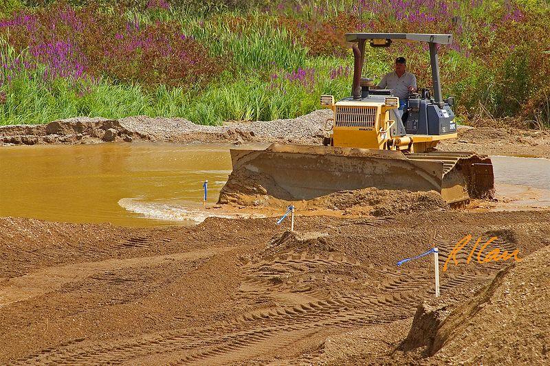 Earthmoving construction: Komatsu D61PX crawler tractor bull dozer moves granular soil out of collected water. Dixboro Bridge, Ann Arbor, 2004.