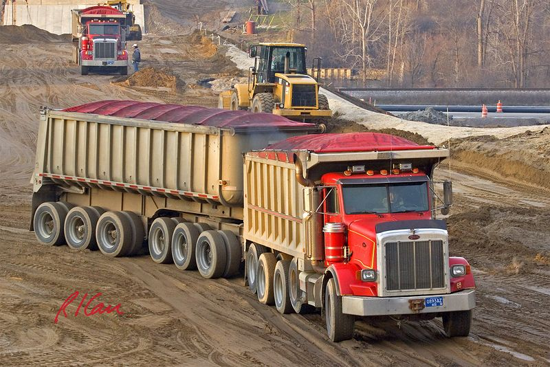 Earth moving construction trucks: Peterbilt tandem rear end dump trucks deliver soil to build up South side ramps for Dixboro Bridge. Dust cover has been pulled over top of truck/trailer beds to stop dust and other debris from blowing out while traveling on roads. Ann Arbor, MI, 2002.