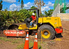 Earth moving/soil construction: Dynapac single drum vibratory soil compactor/ roller being pulled out of mud hole by steel chain attached to large front end loader. Naples, Florida November 2005