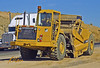 Earthmoving construction: Caterpillar 613C self-loading scraper moves earth for highway rehab. Scraper has 175 hp engine pulling 11 cubic yard bowl. US 405 highway between Los Angeles and Las Vegas, 2005.