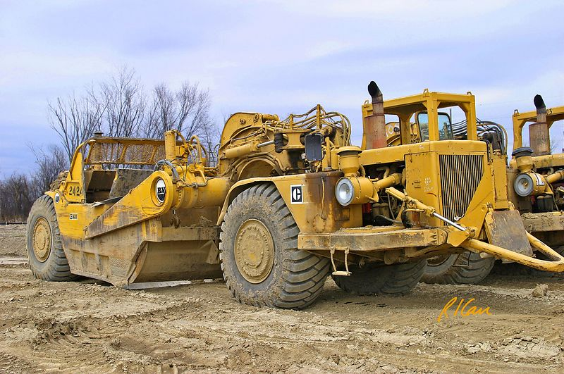 Site construction: Caterpillar 637 wheel tractor scraper, front left view showing front pull engine, 34 cu yd (heaped), 24 cu yd (struck) pan, preparing building sites, Geddes Road, Ann Arbor, 2004.