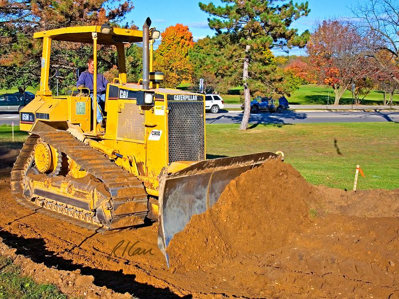 Soil construction, earth moving: Caterpillar D5M 110 hp track mounted bull dozer pushes earth into position for front end loader to pick it up and deliver it to another part of project. Huron Parkway, Ann Arbor, Michigan 2005.