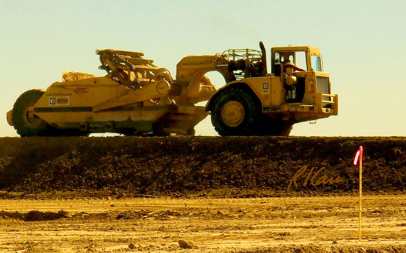 Caterpillar 623B self elevating scraper doing cut and fill to prepare land for development between Phoenix and Tucson, Arizona. Scraper filled its bowl doing cut and raised bowl to travel. It has now lowered bowl and its ejector is pushing the soil load out the front of lowered bowl to dump the load. November, 2006.