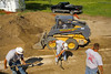 Landscape/earthmoving construction: New Holland LS 180 wheeled skid steer tractor with shovel picks up soil dug out by workers digging shallow trench.  Washtenaw County Farm Park, Ann Arbor, Michigan June 2006.