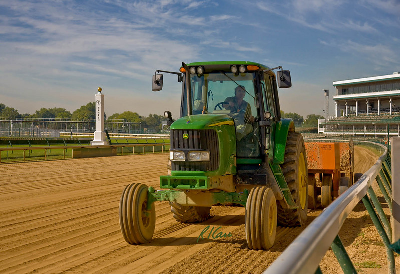 John Deere 7220 tractor pulls rubber tire compactor around dirt track track to compact it for training thoroughbred race horses. Churchill Downs, home of Kentucky Derby, Louisville, Kentucky, September 13, 2007.