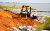 Earthmoving, embankment, shore construction: Deere 450J LGP bull dozer, 74 hp, 17,525 lb, moves/rough grades sand of Pensacola Bay/Gulf of Mexico embankment to be loaded on trucks by backhoe for transport away from site. Pensacola, Florida June 2006.