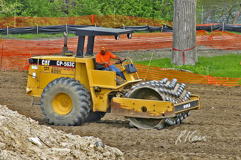 Bridge construction: Caterpillar CP563C single drum vibratory padfoot soil compactor. Broadway Bridge, Ann Arbor, 2003.