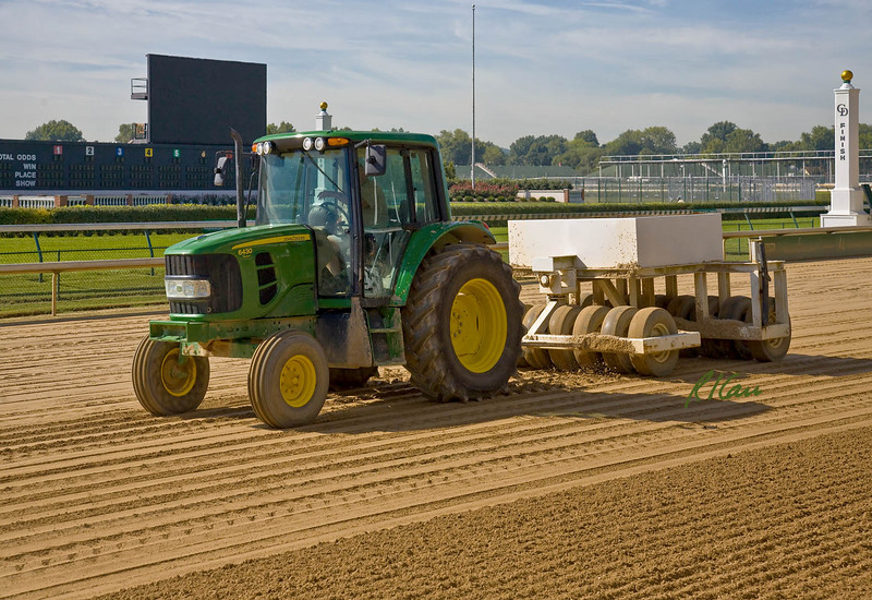 John Deere 6430 tractor pulls rubber tire compactor around dirt track track to compact it for training thoroughbred race horses. Churchill Downs, home of Kentucky Derby, Louisville, Kentucky, September 13, 2007.
