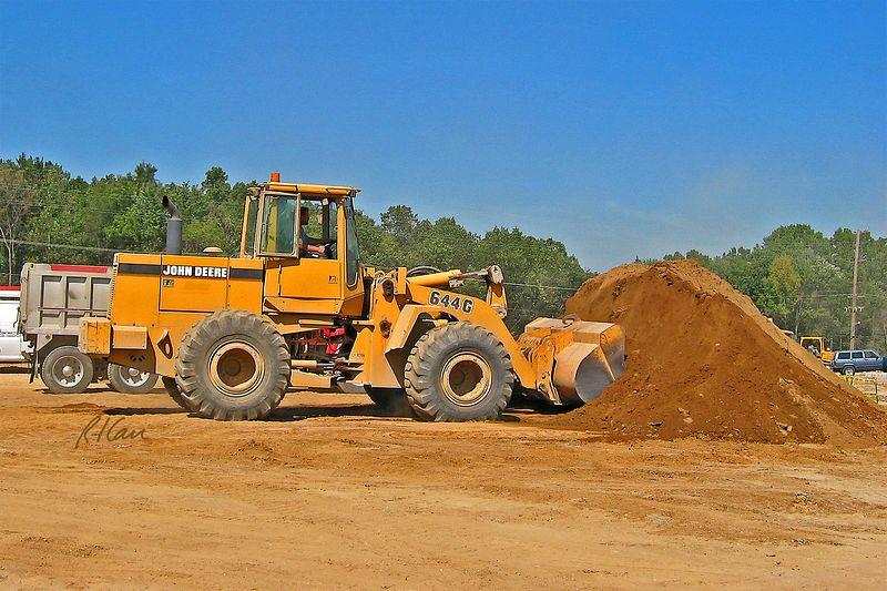 Site construction: John Deere 640C front end loader loads bucket of soil to load truck in background. Huron Village Shopping Center, Ann Arbor, 2002.
