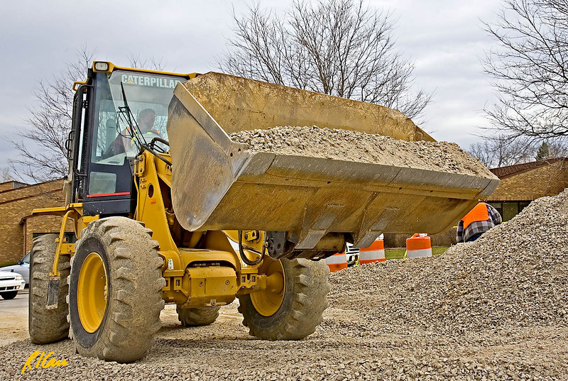 Earthmoving construction: Caterpillar 924G articulated wheel loader moves gravel from stack to base for new road and consolidates gravel pile. Articulated steering is provided by hinging/jointing between cab and front wheels, which provides tight loading and turning radius. The turbocharged diesel engine drives the loader at up to 24 mpg forward and 13.4 mpg backwards. Michigan 2006.