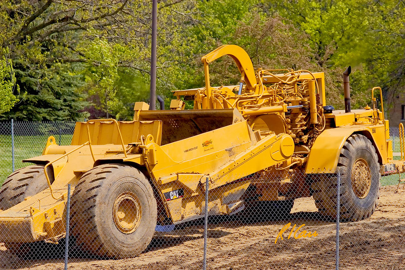 Caterpillar 621F wheel-tractor scraper travels uphill empty, with bowl raised for traveling. The Courtyards private dormitory, North Campus, University of Michigan, Ann Arbor, Michigan. 2007.