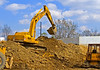 Soil, earth construction: John Deere 892D-LC track mounted hydraulic backhoe excavator digs shovel full, turns, dumps, and turns to fill again. Dixboro Bridge, Huron River, Ann Arbor, Michigan 2005.
