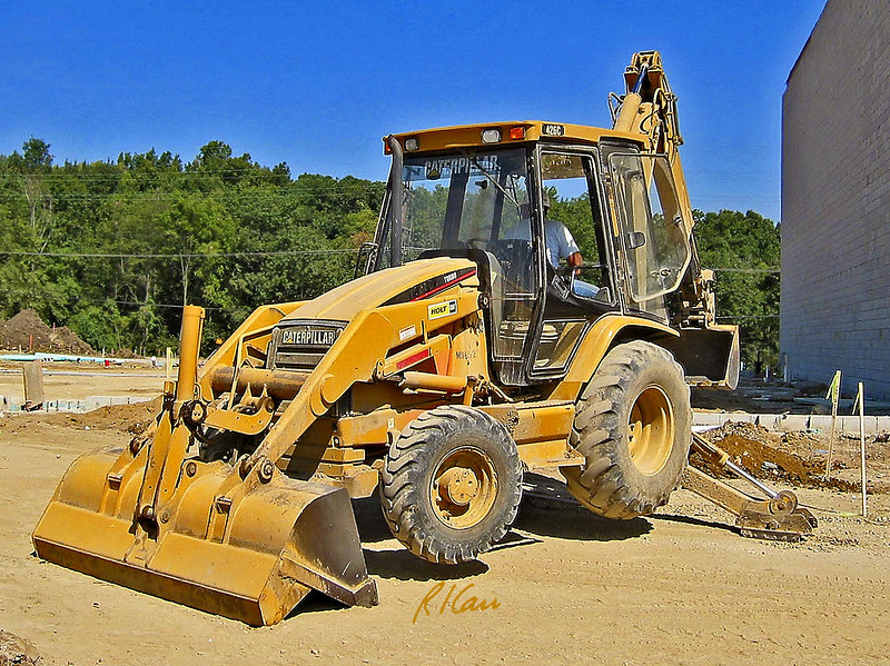 Soil, earth construction: Caterpillar 426C diesel powered, wheel-mounted, backhoe/loader digging a trench, resting on outriggers and loader bucket, with all four wheels in the air. Huron Village Shopping Center, Ann Arbor, 2002.