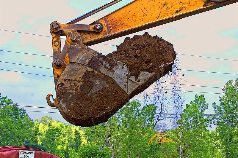 Caterpillar 350 crawler mounted hydraulic backhoe bucket full of soil and then dumping its load. Dixboro Bridge, Ann Arbor, 2004.