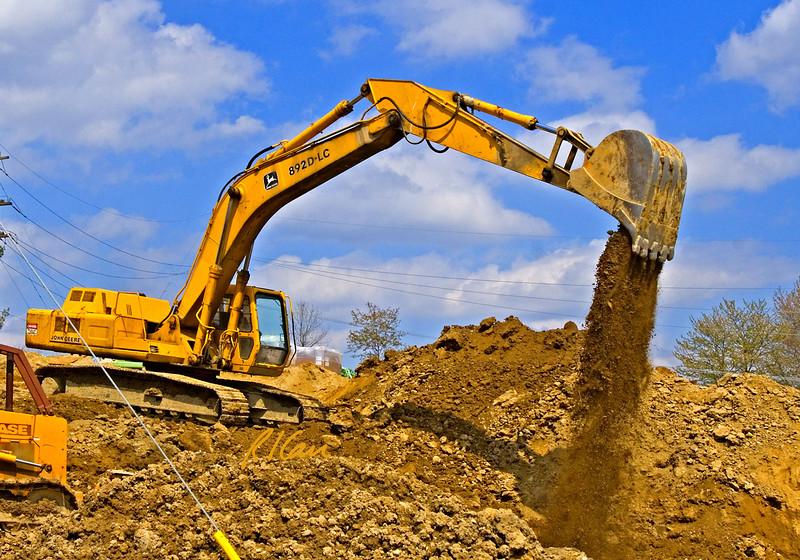 Soil, earth construction: John Deere 892D-LC track mounted hydraulic backhoe excavator digs shovel full, turns, dumps, and turns to fill again. Dixboro Bridge, Huron River, Ann Arbor, Michigan 2005.
