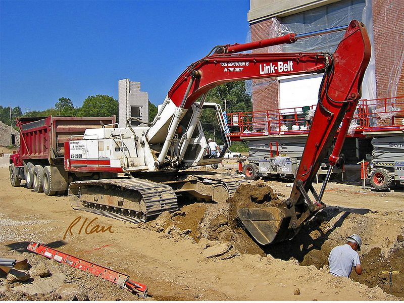 Link Belt LS-2800 crawler mounted hydraulic construction backhoe lifts bucket of soil from 5 ft deep trench. Huron Village Shopping Center, Ann Arbor, 2003.