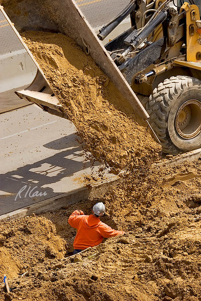 Caterpillar IT38G integrated tool carrier, fitted with side dump bucket, backfills trench under direction of worker with shovel. Mott Childrens Hospital, University of Michigan, Ann Arbor, Michigan. 2007.