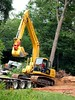 Site construction: Komatsu PC200LC crawler mounted hydraulic backhoe mounts a lowboy trailer