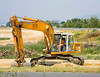 Earthmoving/highway construction/equipment: Liebherr backhoe excavator moves earth of road embankment. Budapest, Hungary July 2006.