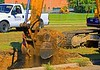 Earthmoving construction: Kobelco 907 LC-II crawler mounted, hydraulic backhoe excavator excavates bucket of earth to load International 7500 HT530 rear dump truck to haul earth away. Huron Parkway at Huron High School, Ann Arbor, Michigan August 2005.