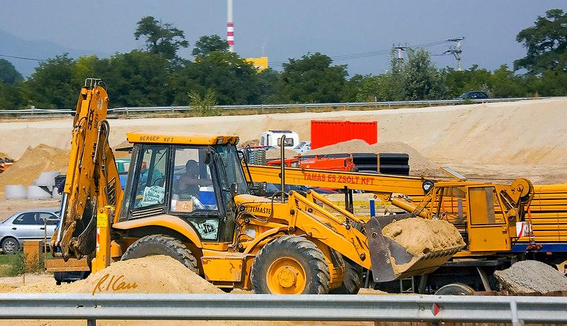 Earthmoving/highway construction/equipment: JCB backhoe/loader carries loader bucket of soil. Budapest, Hungary July 2006.
