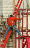 Construction safety, fall protection: Worker is contorting himself reaching with his arm and foot around side of ladder, without using his fall protection. Ladder is itself a hazard, because it is supported at top by a rung against the vertical edge of the gang form. It has a loose wire tied around it and concrete bulkhead at top that provides no useful safety. Practice and OSHA law require top of the ladder to be supported equally by its two side rails. Worker carries two safety lanyards and hooks, attached to full body harness and hooked temporarily at his right chest. Michigan 2006.
