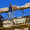 Masonry construction safety, fall hazard: Laborer/ hod carrier stands on top of 3 ft high unstable stack of concrete block and 19 ft above ground, leaning out and stacking heavy blocks, with no fall protection from safety line or guardrail. Ann Arbor, 2004.