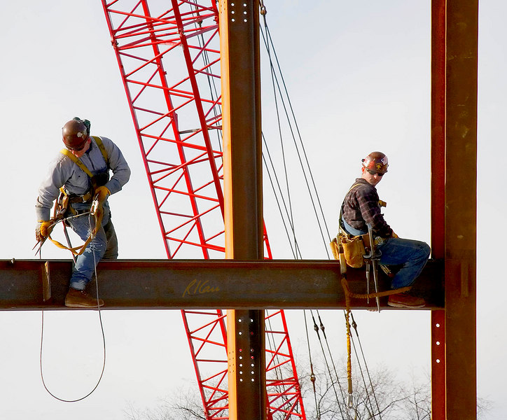 Steel erection fall protection: Structural steel ironworker on left has fall protection from full body harness attached to safety lanyard attached to steel cable loop/sling around girder as he moves from left to right along wide flange structural steel girderl Here, he liftis cable loop/sling past steel plate attachment that will support far end of a steel floor beam/joist. Ironworker on right his apparently without fall protection, with one safety lanyard attached from cable loop/sling that hangs loose and other end attached to lower ring on his body harness. However, his second lanyard could be attached to a sliding beam flange anchor attached to top flange of girder. Ross School of Business, University of Michigan, Ann Arbor. January, 2007.