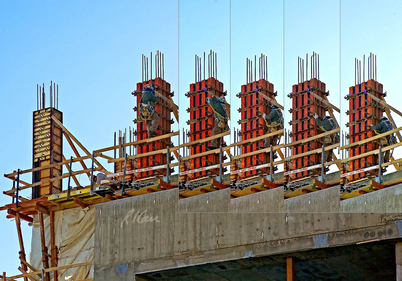 Reinforced concrete structure construction: Carpenter climbs down column formwork using column form horizontal support clamps as steps, hand holds, and fall protection anchor points. The column is between the 4th and 5th floors, so carpenter is 45-50 ft above ground next to edge of floor as he climbs and works on outside of column formwork. Photo shows 5 stages, starting at left and moving to right as carpenter climbs down. He is wearing full body harness, with two safety lanyards hooked to the midbody rear ring. At start, his left side lanyard, hidden from view, is hooked to a support bracket to his front right near his right hand, and the right side lanyard is hooked to another body ring. 2nd photo shows this as he steps down and to right side. At 3rd photo he has hooked end of lanyard to 3rd clamp/bracket from top. He has stepped down in 4th photo and released and hooked to 4th clamp down in 5th photo. Carpenter is wise to use fall protection, which would have been improved if he had used both safety lanyards, hooked to one as the other is moved between anchors. Denver, Colorado December 2005.
