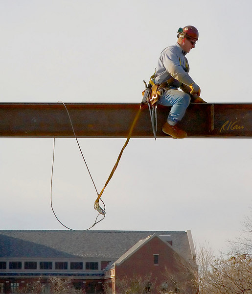 Steel erection fall protection: Structural steel ironworker straddles wide flange structural steel beam. Fall protection provided by full body harness attached to safety lanyard attached to steel cable loop/sling around beam. Ross School of Business, University of Michigan, Ann Arbor. January, 2007.