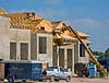Construction safety, building construction: Two workers install plywood sheathing on roof trusses on 2-story residential building. Workers are standing on previously erected sheathing, at a significant slope, without fall protection. They carry the 4'x8' sheets of plywood sheathing as they need them from the Caterpillar hydraulic telescoping boom 4-wheel drive rough terrain forklift. One slip and a worker rolls down roof and falls ~20' off edge or hits open trusses and may fall through them. Fort Myer Beach, Florida 2005