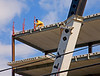 Construction methods, construction safety, fall protection: Worker is attaching stanchions on edge of precast hollow core concrete slabs and steel beam top flanges at roof perimeter of 5-story building. Wire cables will be run at top and midheight of stanchions to provide fall protection to construction workers on roof, in parallel with the cables shown on the perimeter of 5th floor below. However, worker erecting stanchions does not himself have any fall protection, though working at roof edge ~60 ft above the ground. In addition, there may be snow/ice patches on the roof this cold February week. Ann Arbor, Michigan, February 2006.