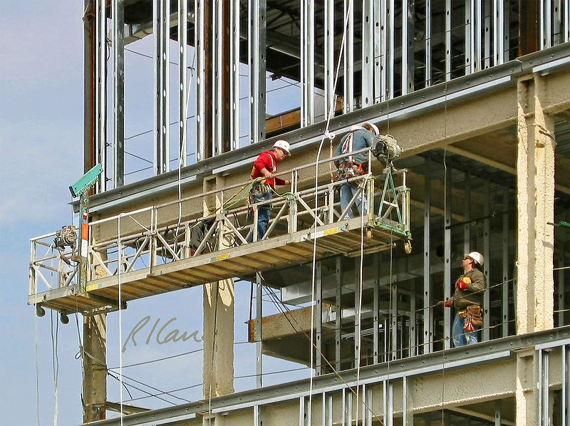 Construction scaffold safety: Manufactured two-point suspended scaffold/ swing scaffold with integrated guardrails provides safe, productive, and ergonomic work platform for  workers placing sheet metal studs for exterior wall cladding. Each worker has his own fall arrest system with body harness, safety lanyard, and vertical lifeline attached to a fixed anchorage above that is separate from the scaffold. Ann Arbor, 2004.