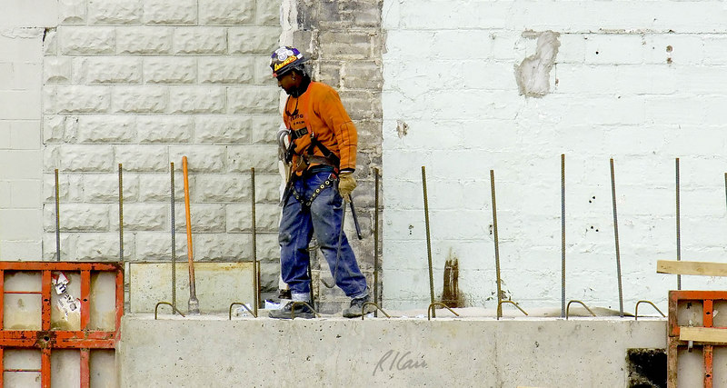 Construction safety, fall protection: Worker walks along top of concrete basement wall more than 20 feet above the ground, among reinforcing bar tripping hazards, without any fall protection. He carries two safety lanyards and hooks, attached to full body harness and hooked temporarily at his right chest. He has duct tape around bottom of his pants so pants do not catch and trip himl. Michigan 2006.