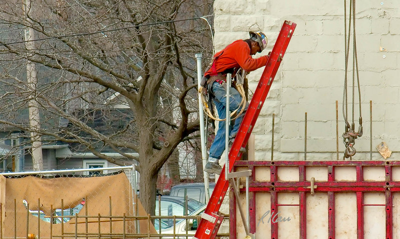 Construction safety, fall protection: Worker has contorted himself around top of ladder, without using his fall protection and is now descending ladder. Ladder is itself a hazard, because it is supported at top by a rung (on which he is placing his bottom foot) against the vertical edge of the gang form. Practice and OSHA law require its top to be supported equally by its two side rails. He has walked along top of concrete basement wall more than 20 feet above the ground, among reinforcing bar tripping hazards, without any fall protection. He carries two safety lanyards and hooks, attached to full body harness and hooked temporarily at his right chest. Michigan 2006.