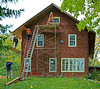 Fall hazard, unsafe scaffold/ladder, construction safety: Upper work, on ladder, is nailing boards to underside of roof to form a new soffit. Worker standing on scaffold work platform hands the nailer each soffit board. He is standing 12 foot above ground, without fall protection from standard guardrails or personal fall protection gear, and this is a serious fall hazard. A 6 foot stepladder stands on unguarded scaffold platform 20 feet above ground. Therefore, worker(s) worked on stepladder at least 23 feet above ground without using fall protection. Ladder should be tied off at top to scaffold. Ann Arbor, Michigan 2005
